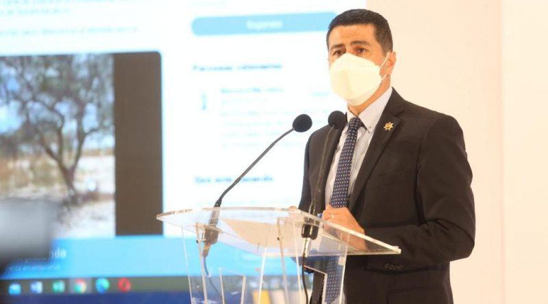 Secretario de Seguridad de Michoacán Israel Patrón en dando un discurso con una pantalla mostrando un video a sus espaldas