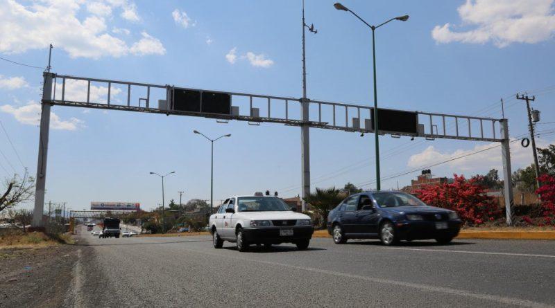 Dos vehiculos que circulan en una avenida donde hay cámaras de vigilancia