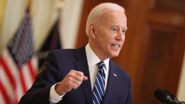 Joe Biden presidente de estados unidos discursando con la bandera de estrellas y rayas detrás de él