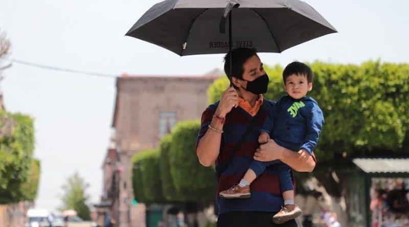 papa camina en el centro de morelia cubriendo del sol a un niño de brazos